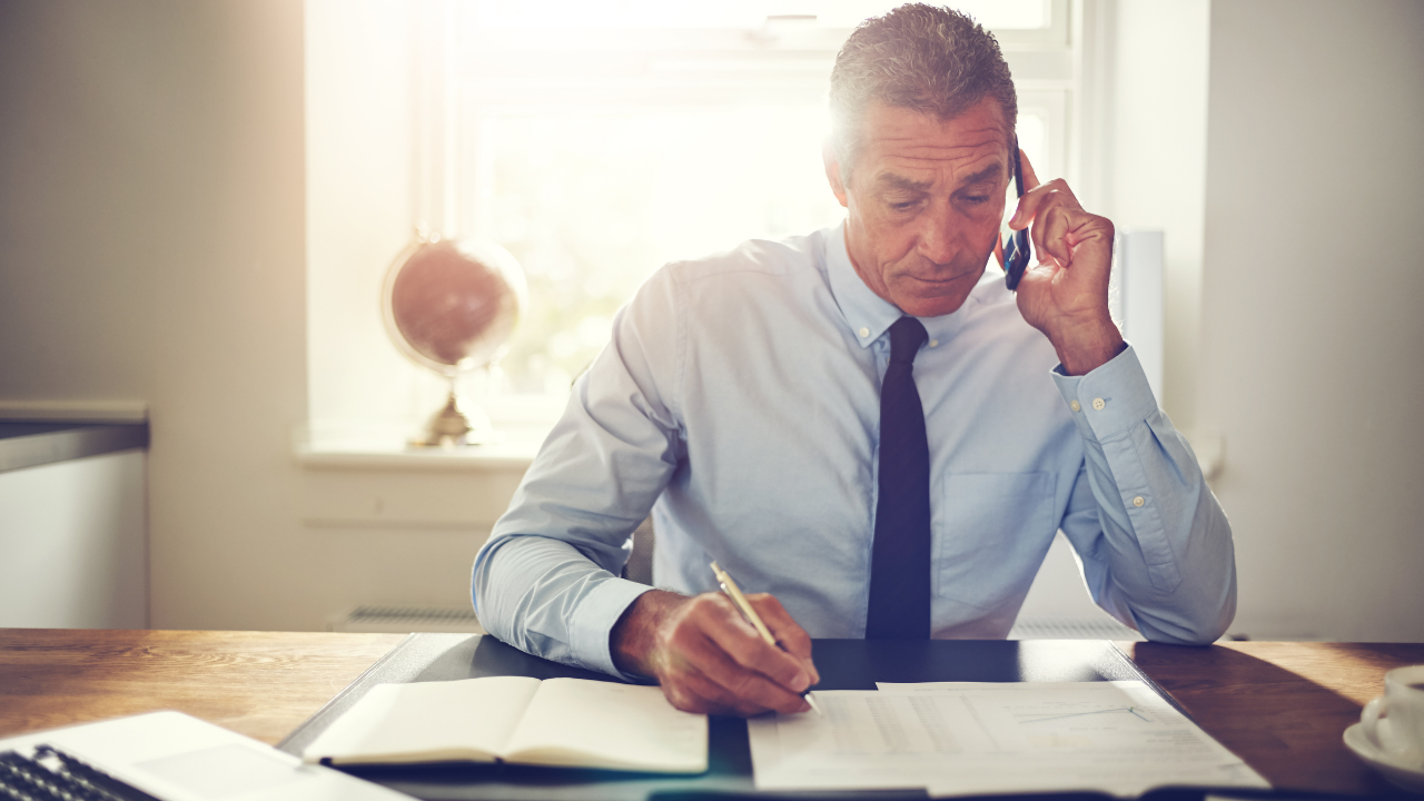 Business man seated at desk looking at paperwork